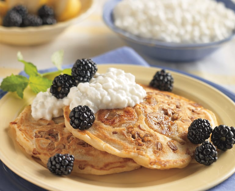 banana granola pancakes on plate with cottage cheese and blackberries on top