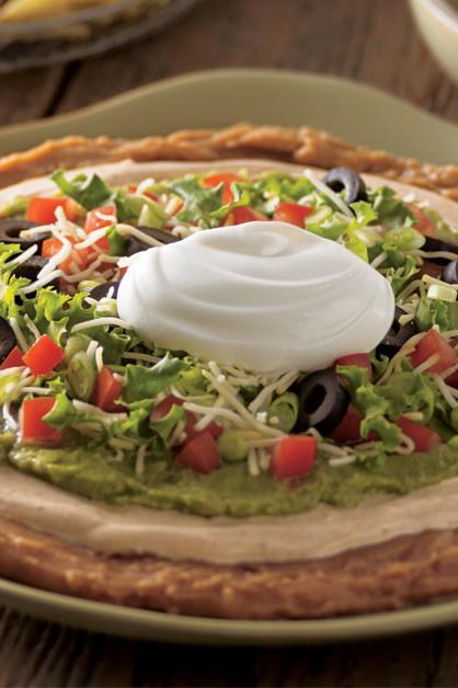 Dip mexicano de frijoles en capas en un plato con crema agria