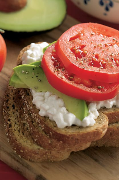 Open Faced Hearty Wheat Sandwich with bread sliced, cottage cheese, avocado, and tomato