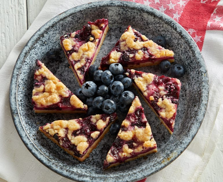 Blueberry Pie Bars on a plate with blueberries