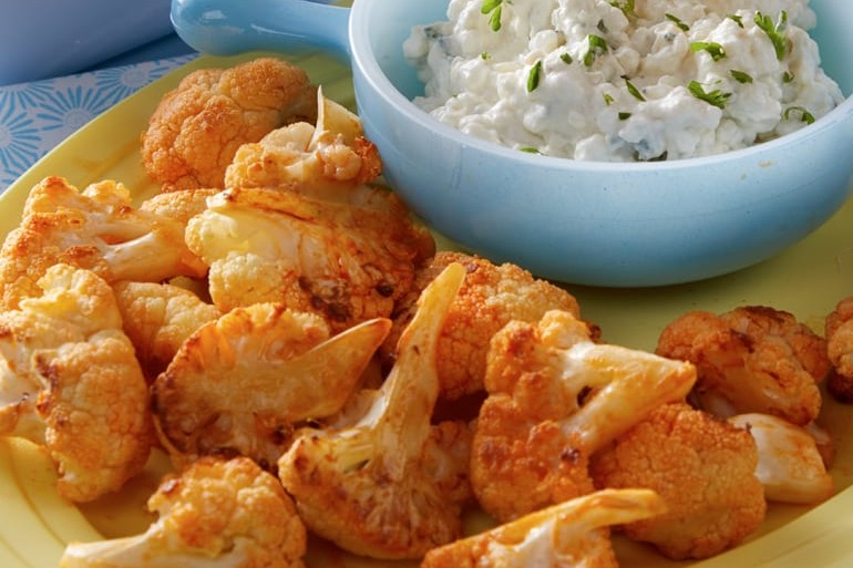 buffalo roasted cauliflower on plate with a side of cottage cheese